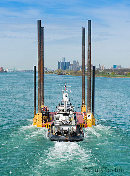 Aerial photography over the Detroit River. Low level aerial photograph of tug boat pushing a jack up barge down the Detroit River.