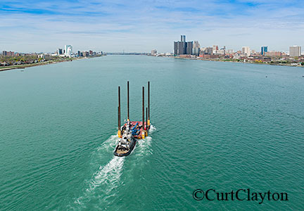 Aerial photography over the Detroit River. Aerial photograph of tug boat pushing a jack up barge down the Detroit River.