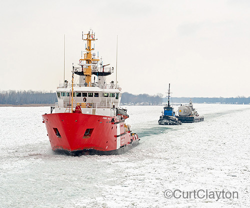Aerial photograph of CCGS Samuel Risley leading a barge through the ice in the St. Clair River north of Detroit