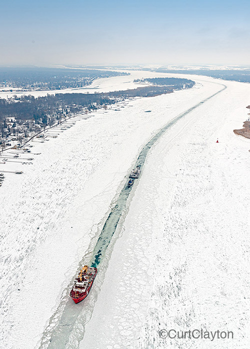 Aerial photograph of a barge being brought through the ice in the St. Clair River north of Detroit